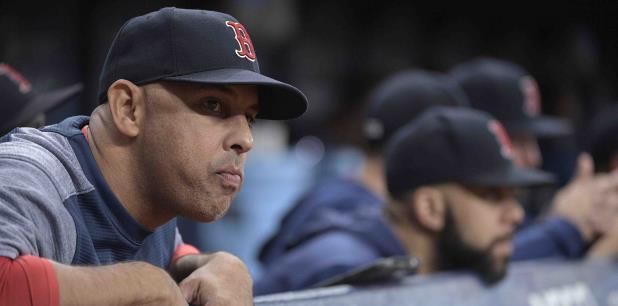 El dirigente puertorriqueño Alex Cora observa desde el dugout el partido en el que sus Medias Rojas fueron dejados en el terreno por los Rays. (AP)
