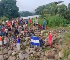 Migrantes en caravana cantan el himno de Honduras tras cruzar a México